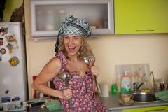 Retrato engraçado da dona de casa na cozinha Imagens de Stock