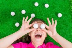 Retrato engraçado de uma mulher com bolas de golfe Fotos de Stock