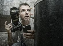 Retrato engraçado do estilo de vida do homem novo do fotógrafo dos paparazzi na ação escondido atrás da cesta do papel da cidade  imagem de stock royalty free