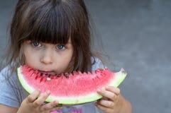 Retrato engraçado dos olhos azuis incredibly bonitos de uma menina, comendo a melancia, petisco saudável do fruto imagem de stock