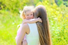 Retrato ensolarado da criança feliz que abraça a mãe no verão Imagens de Stock