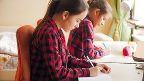 Retrato entonado de dos muchachas que hacen la preparación detrás del escritorio en la ventana grande Fotografía de archivo libre de regalías