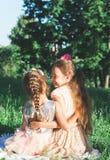 Retrato entonado de dos niñas felices que abrazan y que pasan fotos de archivo