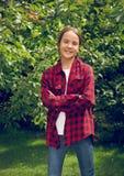 Retrato entonado de la chica joven sonriente en la camisa a cuadros que presenta a Fotos de archivo libres de regalías