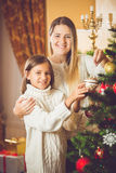 Retrato entonado de la madre de ayuda sonriente Christm de adornamiento de la muchacha Foto de archivo