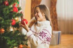 Retrato entonado de la muchacha linda en suéter que adorna el árbol de navidad Imagen de archivo