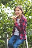 Retrato entonado del adolescente hermoso que se sienta en la escalera de mano en la huerta y que come la manzana fresca Fotos de archivo libres de regalías