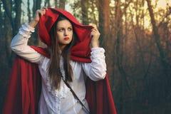 Retrato escuro de pouca capa de equitação vermelha fotografia de stock