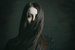 Retrato escuro de uma jovem mulher