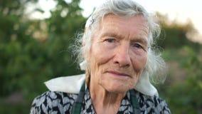 Retrato expresivo mismo de una mujer mayor Una mujer jubilada canosa en una bufanda mira atento el marco La abuela es almacen de metraje de vídeo
