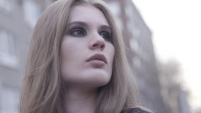 Retrato exterior da beleza da menina de cabelo marrom nova que olha de lado sobre o perímetro urbano borrado fundo a??o Feche aci vídeos de arquivo