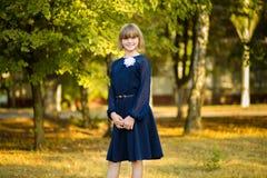 Retrato exterior da estudante pequena feliz na farda da escola no parque De volta à escola foto de stock royalty free
