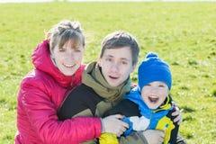 Retrato exterior da família do dia ensolarado de três povos alegres no parque foto de stock