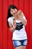 Retrato exterior da forma do close up da menina louca do moderno novo que come o gelado no tempo quente do verão, tendo o diverti foto de stock