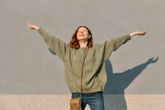 Retrato exterior da menina adolescente feliz com m?os acima e olhos fechados, fundo ensolarado cinzento da parede, emo??o da feli foto de stock royalty free