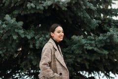 Retrato exterior da menina bonita nova no tempo frio do inverno no parque fotografia de stock