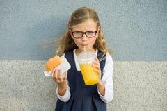 Retrato exterior da menina da criança com cabelo encaracolado louro com vidros A menina come o sanduíche e bebe o suco de laranja imagens de stock royalty free