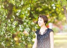 Retrato exterior da menina da mola em árvores de florescência Mulher romântica da beleza nas flores Senhora sensual Mulher bonita Fotos de Stock Royalty Free