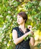 Retrato exterior da menina da mola em árvores de florescência Mulher romântica da beleza nas flores Senhora sensual Mulher bonita Foto de Stock