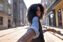 Retrato exterior da mulher de pele escura atrativa com cabelo encaracolado que aprecia o tempo agradável ao andar em torno da cid foto de stock royalty free