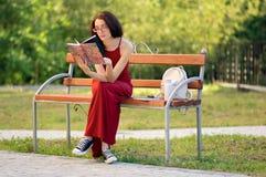 Retrato exterior de la mujer joven en libro de lectura de la ropa casual en el parque de la ciudad durante Sunny Warm Day en el v Imágenes de archivo libres de regalías