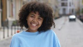 Retrato exterior de rir a menina encaracolado da raça misturada vídeos de arquivo