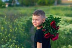 Retrato exterior de um menino em uma caminhada com flores da pe?nia fotografia de stock royalty free