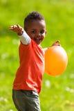 Retrato exterior de um menino preto pequeno novo bonito que joga com Fotos de Stock Royalty Free
