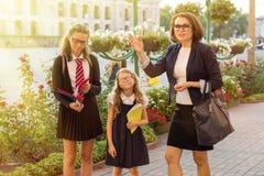 Retrato exterior de um pai e de crianças na maneira à escola fotos de stock royalty free