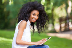 Retrato exterior de uma menina preta adolescente que usa uma tabuleta tátil Fotos de Stock Royalty Free
