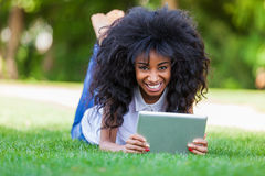 Retrato exterior de uma menina preta adolescente que usa uma tabuleta tátil Imagem de Stock Royalty Free