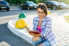 Retrato exterior de uma mulher bonita adulta que lê um whil do livro fotos de stock royalty free