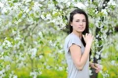 Retrato exterior de uma mulher bonita na árvore de florescência na mola Fotografia de Stock Royalty Free