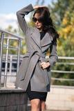 Retrato exterior de uma mulher elegante bonita nova, fora Um modelo vestiu-se em um revestimento cinzento à moda, óculos de sol O foto de stock royalty free