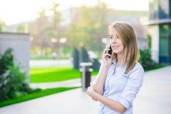 Retrato exterior de uma mulher ou de uma mulher de negócios moreno feliz bonita em seus anos 30 que falam em seu telefone celular Imagens de Stock