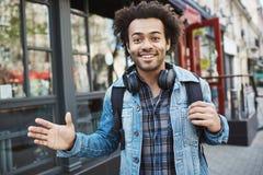 Retrato exterior do afro-americano positivo com o penteado afro que acena e que sorri na câmera ao andar na rua Foto de Stock