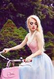 Retrato exterior do encanto de uma menina loura 'sexy' que monta uma bicicleta no parque Fotografia de Stock Royalty Free