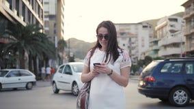 Retrato exterior do estilo de vida da jovem mulher que anda abaixo da rua usando Smartphone, curso com trouxa, ocasional à moda Fotos de Stock