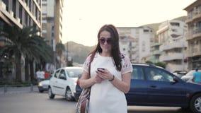 Retrato exterior do estilo de vida da jovem mulher que anda abaixo da rua usando Smartphone, curso com trouxa, ocasional à moda Imagem de Stock Royalty Free