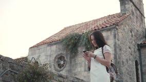 Retrato exterior do estilo de vida da jovem mulher que usa Smartphone, curso com trouxa, equipamento ocasional à moda, nivelando  filme