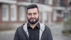 Retrato exterior do homem de sorriso considerável novo com barba filme