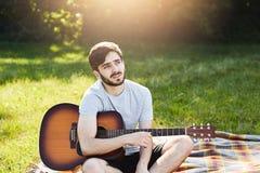 Retrato exterior do homem novo atrativo com a barba vestida ocasionalmente ao descansar na grama verde com guitarra, tendo o expr fotos de stock royalty free