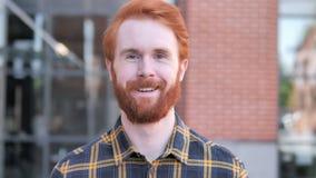 Retrato exterior do homem novo de sorriso da barba do ruivo filme