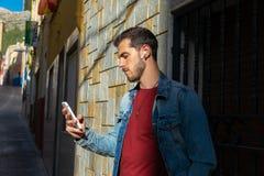 Retrato exterior do homem novo moderno com o telefone esperto na rua fotografia de stock royalty free