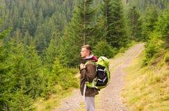 Retrato exterior do homem novo que caminha nas montanhas, retrato feliz de sorriso do homem do turista esporte extremo, equipamen Fotos de Stock