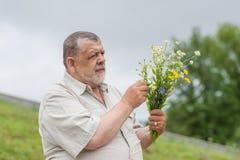 Retrato exterior do homem superior com o ramalhete de flores selvagens para sua esposa imagens de stock royalty free