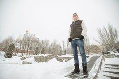 Retrato exterior do inverno para o homem considerável novo Adolescente bonito em seus revestimento e veste que levantam em uma ru fotografia de stock
