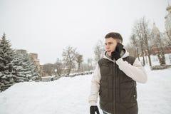 Retrato exterior do inverno para o homem considerável novo com o telefone Adolescente bonito em seus revestimento e veste que lev fotografia de stock