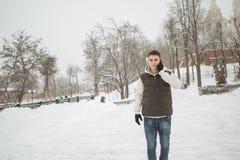 Retrato exterior do inverno para o homem considerável novo com o telefone Adolescente bonito em seus revestimento e veste que lev imagem de stock royalty free