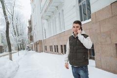 Retrato exterior do inverno para o homem considerável novo com o telefone Adolescente bonito em seus revestimento e veste que lev fotografia de stock royalty free